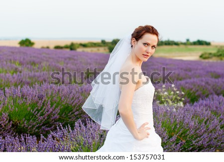 Young white girl with red hair in the form of a bride in a veil at lavender field - stock photo