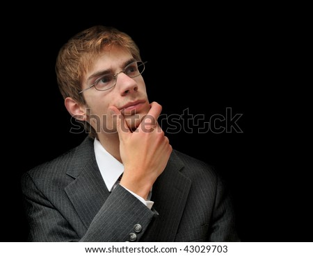 Young white male Caucasian man in suit seriously ponders and questions himself isolated on black background. - stock photo