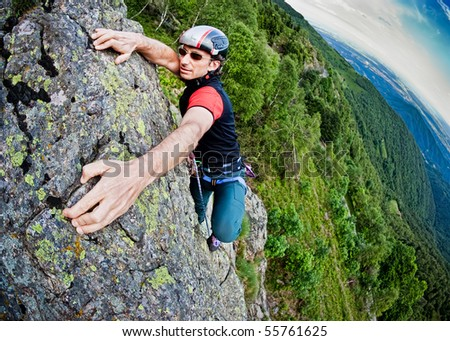 Young white man climbing a steep wall in mountain, rock-climb extreme sport, summer season. Horizontal orientation - stock photo