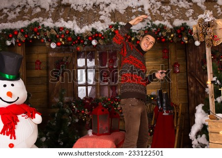 Young White Man Holding Pair of Ice Skates Up at Decorated Wooden House with Winter Snowman and Christmas Booth Decors. - stock photo