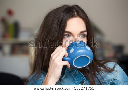 Young white woman drinking refreshment, dotted mug - stock photo