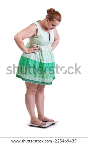 Young white woman with obesity, in dress standing on weight scale isolated on white background - stock photo
