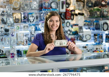 Young white woman working as shop owner in computer store, showing her first dollar to the camera and smiling. Rack focus from woman's face to banknote - stock photo