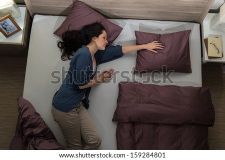 Young widow lying in bed missing her husband - stock photo