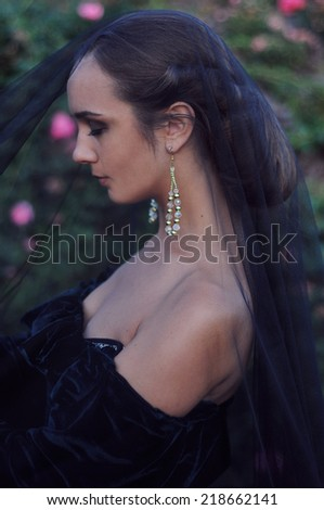 Young widow with closed eyes wearing black veil - stock photo