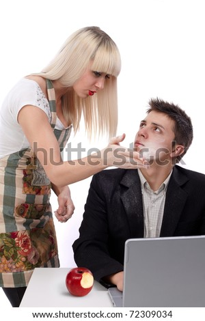 Young wife arguing with her husband because she's working and his sitting at the laptop. He bit also from the forbidden fruit. Concept of the apple of discord. - stock photo