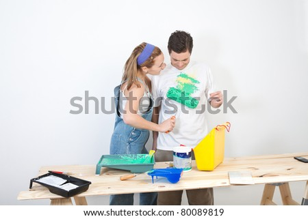 Young wife painting on t-shirt of husband