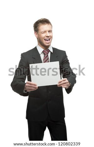 young winking caucasian businessman in black suit holding sign isolated on white - stock photo