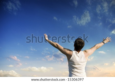Young winner looking at blue sky with clouds - stock photo