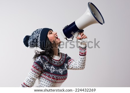 Young winter christmas woman shouting with a megaphone against a white background