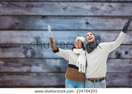 Young winter couple against blurry wooden planks - stock photo