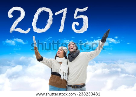 Young winter couple against bright blue sky over clouds - stock photo