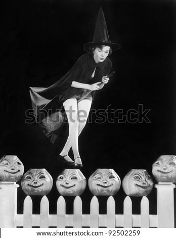 Young witch hovers on her broom, eyeing which pumpkin to choose - stock photo