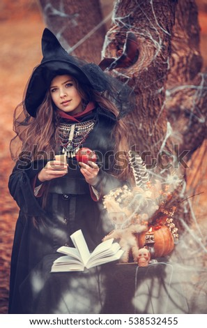 Young witch in peaked hat engaged in witchcraft, halloween, Samhain