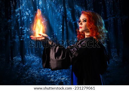 Young witch in the night forest holds fire - stock photo