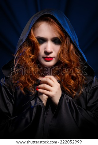 Young witch on blue rays background - stock photo