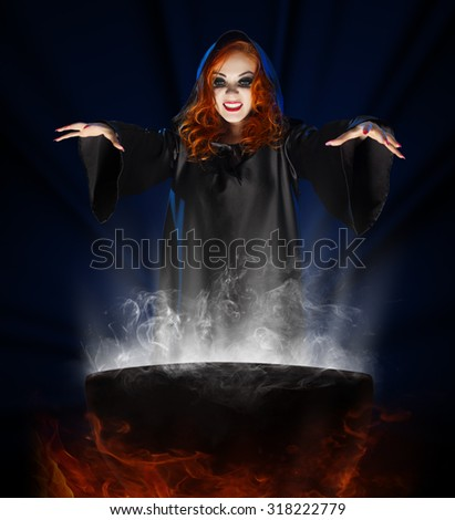 Young witch with cauldron on blue rays background - stock photo