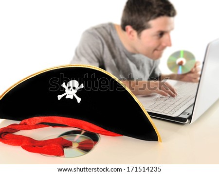 Young with Computer copying dvd and pirate hat representing illegal downloads and copyright violation isolated on white background - stock photo