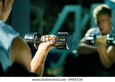 Young with dumbbells, seeing himself in mirror (focus on dumbbells) - stock photo