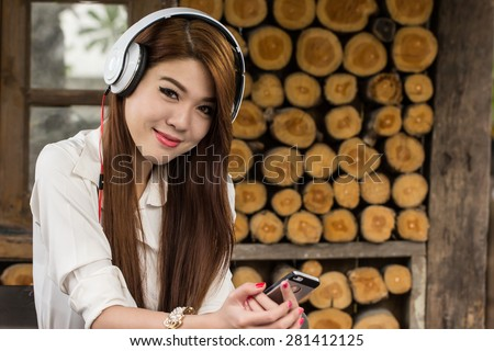 Young woaman enjoying  music with smart phone in coffee shop - stock photo
