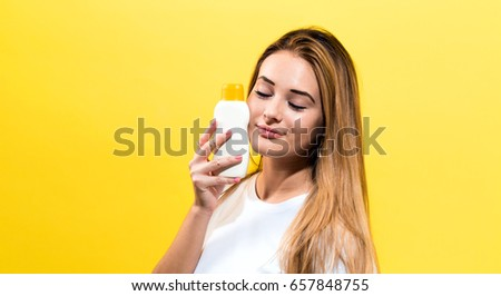 Young woman a bottle of sunblock on a yellow background