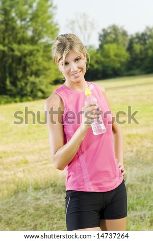 Young woman about to drink from water bottle outdoors after jogging - stock photo