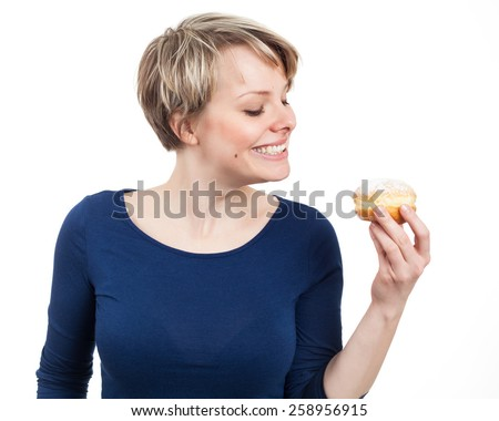 Young woman about to eat a donut, isolated on white - stock photo