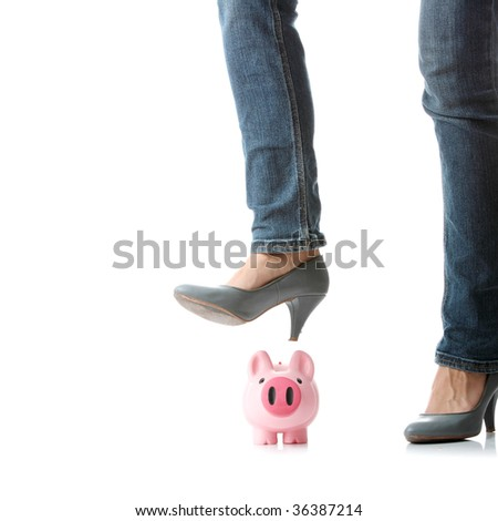Young woman about to smash piggy bank with her leg to get at savings