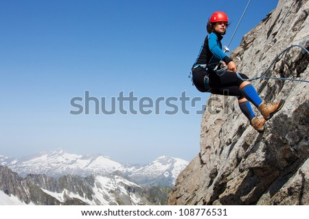 Young woman abseiling rock face in the Alps with large copy space - stock photo