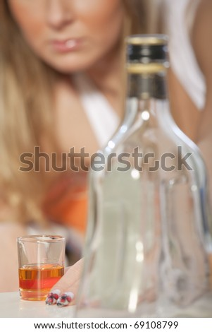Young woman addicted to alcohol - focus on glass - stock photo