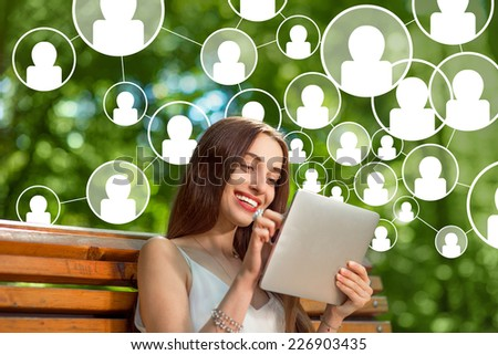 Young woman adding friends in social media with digital tablet in th park - stock photo