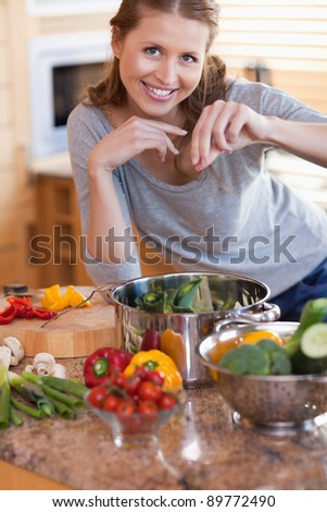 Young woman adding some spices to her meal - stock photo