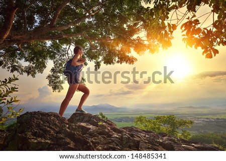 Young woman admires the sunset with a backpack standing on cliff edge - stock photo