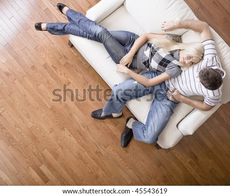 Young woman affectionately lays against a young man on a cream colored love seat. Horizontal shot.