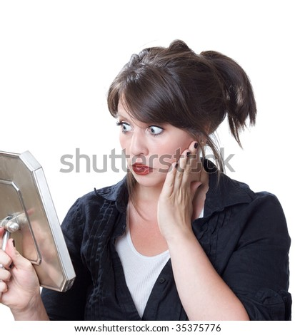 Young woman afraid and fearful of the image she sees in the mirror; isolated on a white background. - stock photo