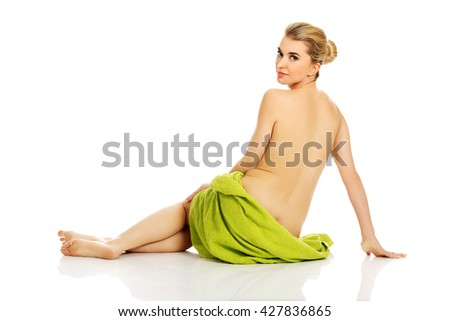 Young woman after bath or spa sitting on the floor wrapped in towel. - stock photo