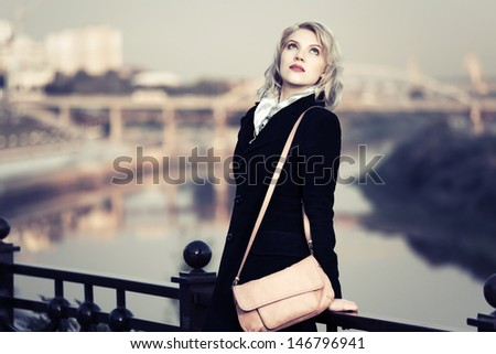 Young woman against an autumn urban background - stock photo
