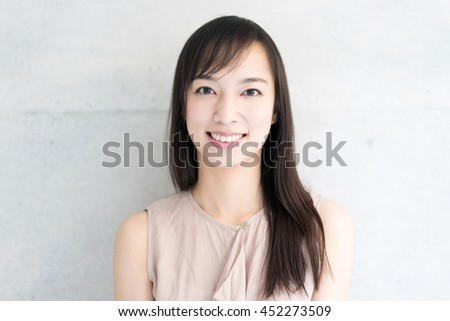 Young woman against concrete wall - stock photo