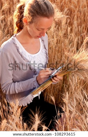 Young woman agronomist or a student with document and ears wheat in hand writes results of her experiment in the wheat field - stock photo