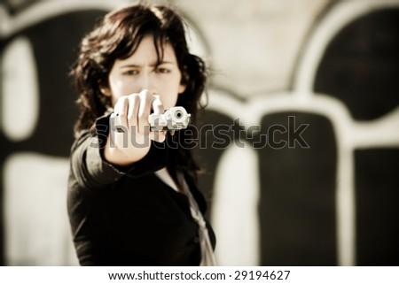 Young woman aiming at the camera. Focus in the gun barrel. - stock photo