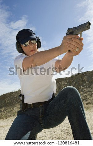 Young woman aiming with handgun at combat training - stock photo