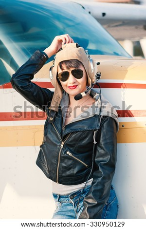 Young woman airplane pilot portrait on landing strip. Filtered image. - stock photo