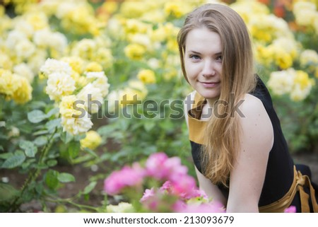Young woman alone and many yellow roses around - stock photo