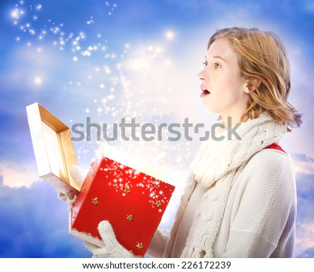 Young woman amazed upon opening a magical Christmas present - stock photo