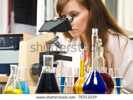 Young woman analyzing samples in a lab - stock photo
