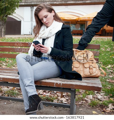 Young woman and a pickpocket stealing from her handbag - stock photo