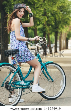 Young woman and bike in city looking at the camera. Active people. Outdoors - stock photo