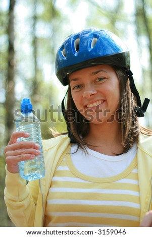 young woman and bike in the forest - stock photo
