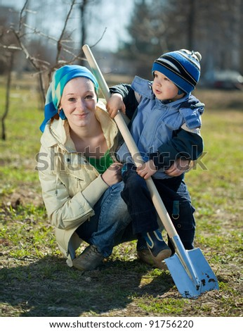 young woman and boy working with spade  in garden - stock photo