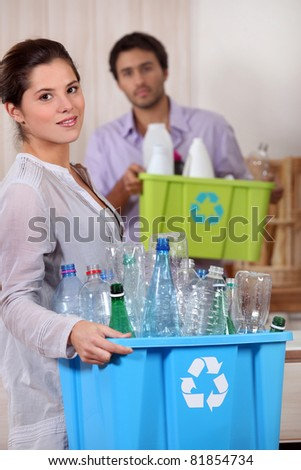 Young woman and boyfriend recycling plastic - stock photo